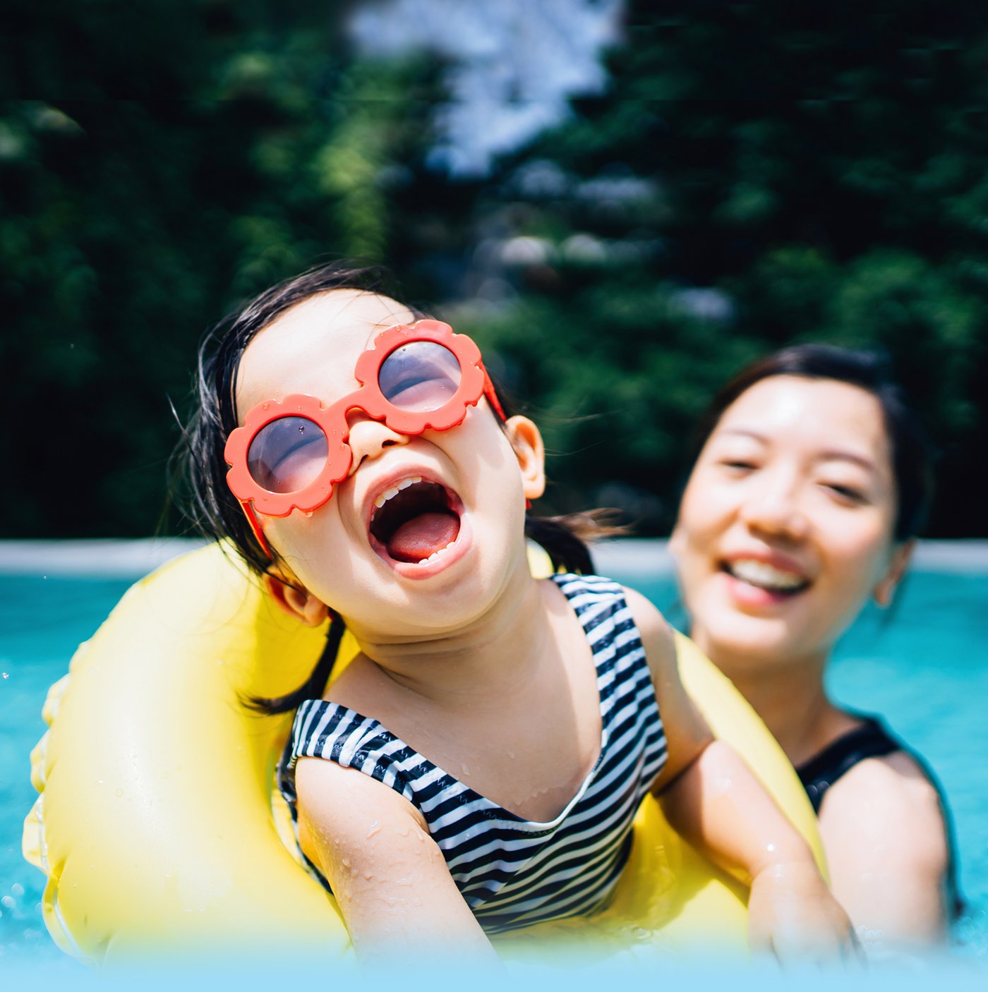 Mother and daughter swimming in a pool